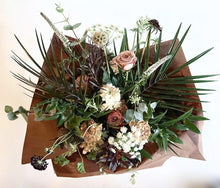 A bouquet bursting with seasonal flowers and foliage in dusky cappuccino, tan and white shades with pops of burgundy and lots of textures and greenery.