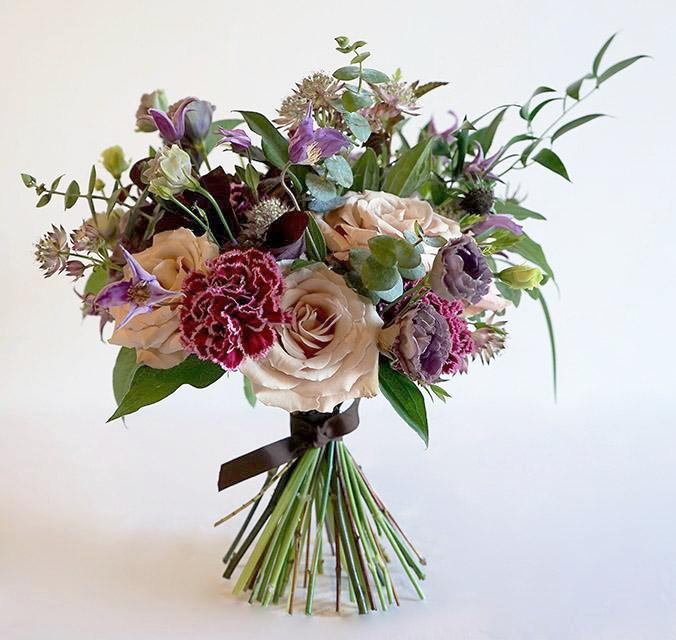 A bouquet full of seasonal summer flowers in a muted pink, lilac and raspberry color palette with lots of greenery and texture.