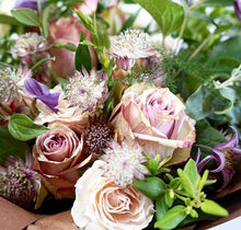 A bouquet full of roses in varying shades of pink, lilac clematis and other summer flowers and foliage.