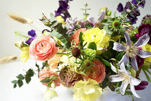 An arrangement bursting with seasonal flowers and foliage and is designed in a lush, asymmetric and horizontal style.