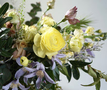 A hand-tied bouquet bursting with seasonal flowers and foliage in shades of yellow and lilac with lots of seasonal greenery and foliages and loads of texture
