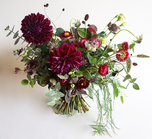 A bouquet full of seasonal flowers in shades of magenta and pink with lots of greenery and texture.