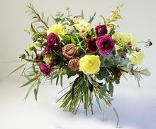A hand-tied bouquet bursting with seasonal flowers and foliage in shades of yellow, scarlet and dusky pink with lots of seasonal greenery and foliages and loads of texture