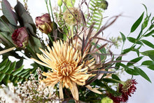 A bouquet full of seasonal flowers in warm autumnal colors.