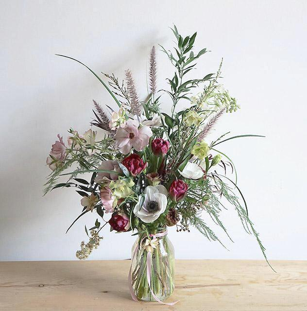 A bouquet bursting with seasonal spring flowers in a pink, white and magenta color palette with lots of different foliages.