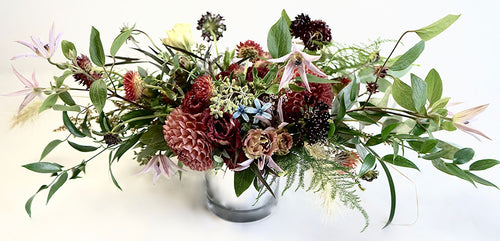 An arrangement bursting with seasonal flowers and foliage designed in a low and horizontal style.