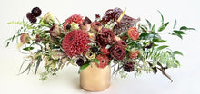 An arrangement bursting with seasonal flowers and foliage and is designed in a low and horizontal style. It makes a perfect gift and is ideal as a table centerpiece.
