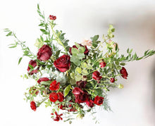 A red rose Valentine's bouquet but with a twist! It is bursting with seasonal flowers and foliage in shades of red and hints of blush with lots of seasonal greenery and foliages and loads of texture.