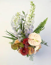 A flower jar bouquet full of seasonal summer flowers in a peach, coral and rusty pink/orange color palette with pops of blue and striking greenery.