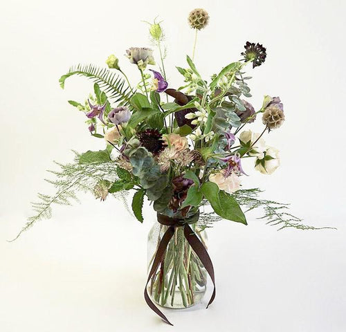 A delicate and airy flower jar bouquet full of seasonal summer flowers in a lilac and pale pink color palette with bursts of greenery and lots of texture.