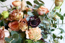 A bouquet bursting with seasonal flowers and foliage in shades of coral and tan with lots of seasonal greenery and foliages and loads of texture.