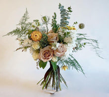 A bouquet full of summer flowers in a soft pale pink and creamy white with pops of yellow and lots of greenery and texture.