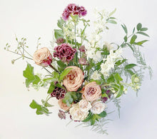 A flower jar bouquet full of seasonal summer flowers in shades of cappuccino, raspberry and scarlet with pops of white and pale pink and lots of greenery.