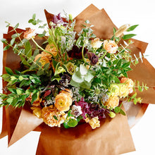 A bouquet bursting with seasonal flowers and foliage in shades of coral, tan, lilac and purple with lots of seasonal greenery and foliages and loads of texture.