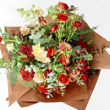A bouquet bursting with seasonal flowers and foliage in shades of red and tan/cappuccino with lots of seasonal greenery and foliages and loads of texture.   This is not your average red rose Valentine's bouquet but perfect for those who love a little red!
