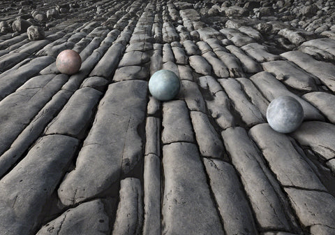 Jurassic rock falls off in perspective to infinity while three planet like spheres sit in line on top.