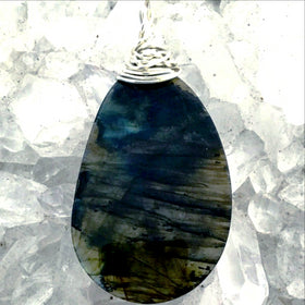 "Labradorite Free Form Slice Pendant shows flashes of blue and gold. The beautiful pendant is 2 ½"" x 1 ¼"" with a wire wrapped bail. Mystical statement piece! New Earth Gifts"