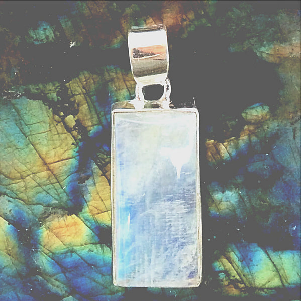 "A Rainbow Moonstone Rectangular Sterling Pendant is just the style for a bold statement! The slender pendant is 1.5"" x .5"" and shows lots and lots of rainbows. New Earth Gifts"