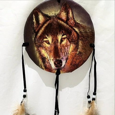 "The Medicine Shield - Wolf Portrait is 6"" round and hangs 24"" from top to bottom of feathers. The image is a close-up of the haunting face of a lone wolf. New Earth Gifts"