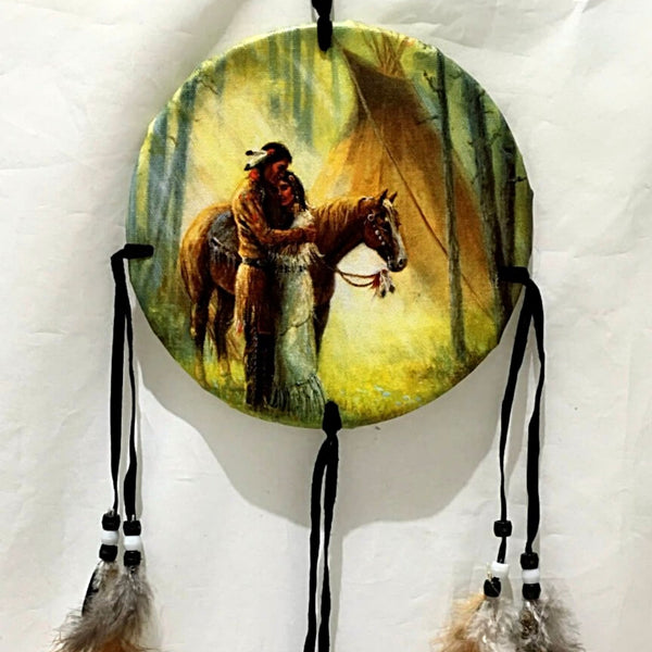 "The Medicine Shield of Native American Couple is 6"" round and hangs 24"" from top to bottom of feathers. The image depicts a loving couple comforting each other. New Earth Gifts"