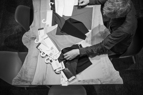 Overhead shot of product designer looking through fabric swatches laid out on a table