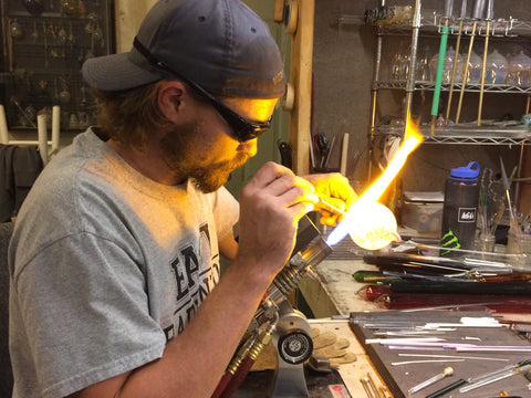 man blowing glass