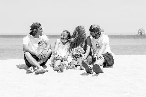 family of 4 sitting on a beach