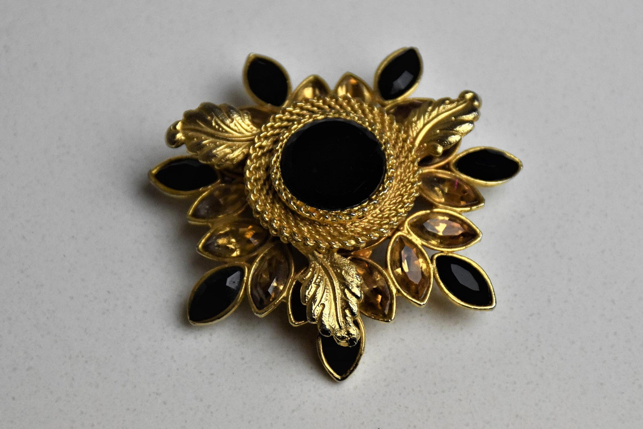 1960's American star burst gold-tone and onyx brooch