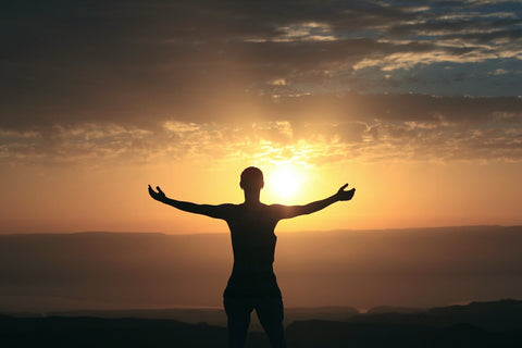 Man standing with open arms looking at sunset