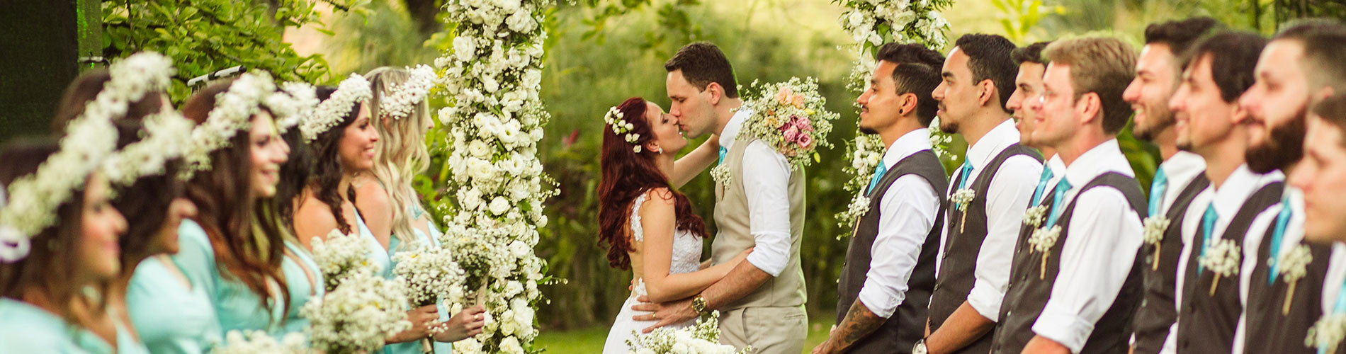 couple getting married under flower arch