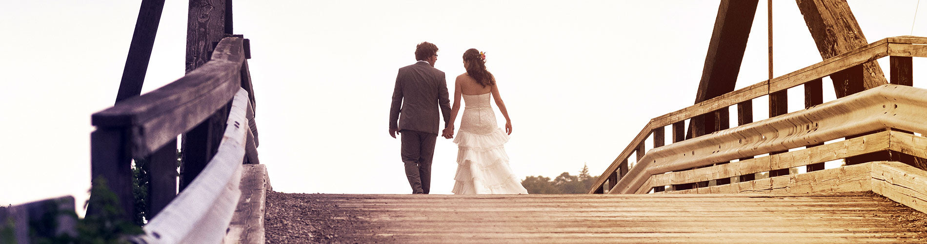 bridal couple walking over a bridge