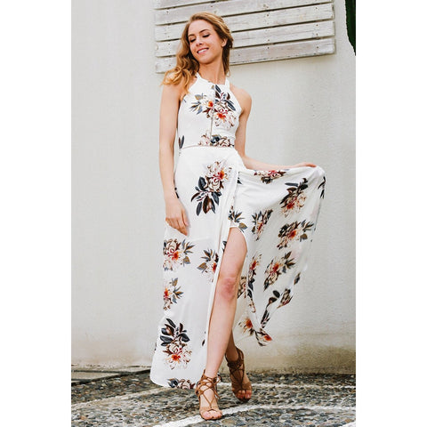 The Simone Dress is a gorgeous halter maxi dress with an open back and tie ribbon, and a sweet floral pattern. Long split for sexy peep leg style!