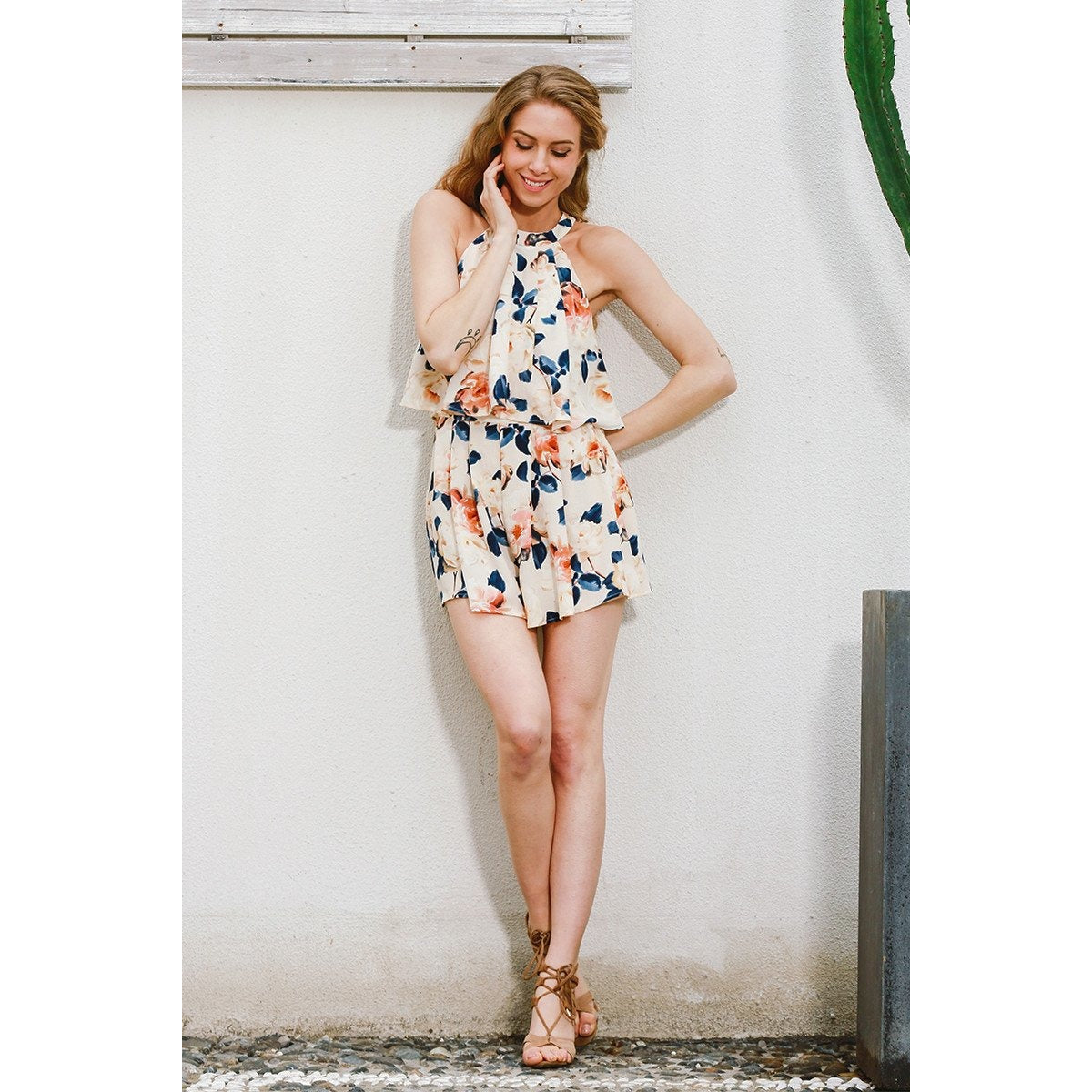 The Bonnie Halter Romper is a sweet playsuit that features a circle halter neckline, sleeveless shorts with a floral pattern and lightly pleated style.