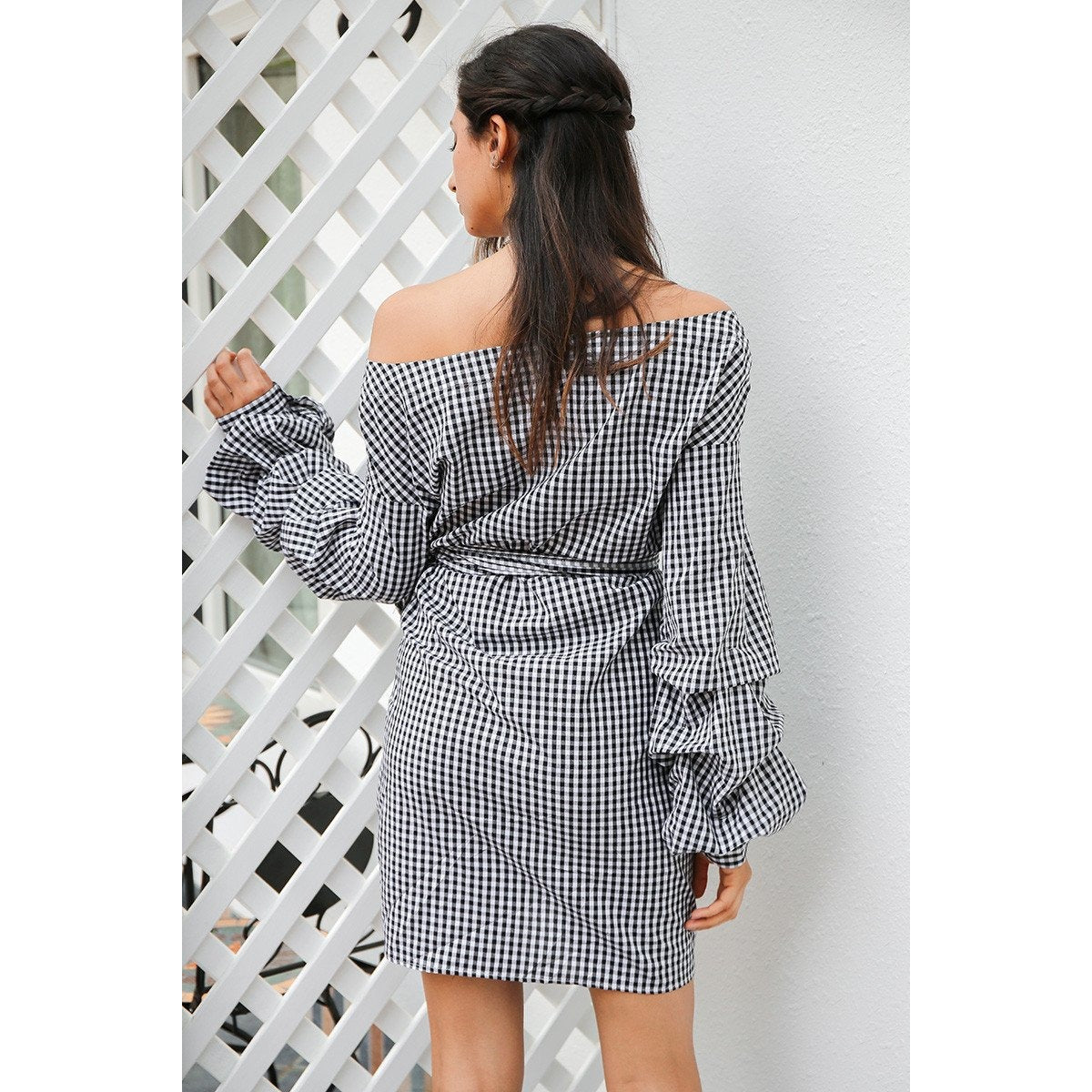 The Leilani Dress is a wrap style mini dress with cold shoulder style design, long lantern sleeves, and a front tie sash. Striped & gingham plaid prints.