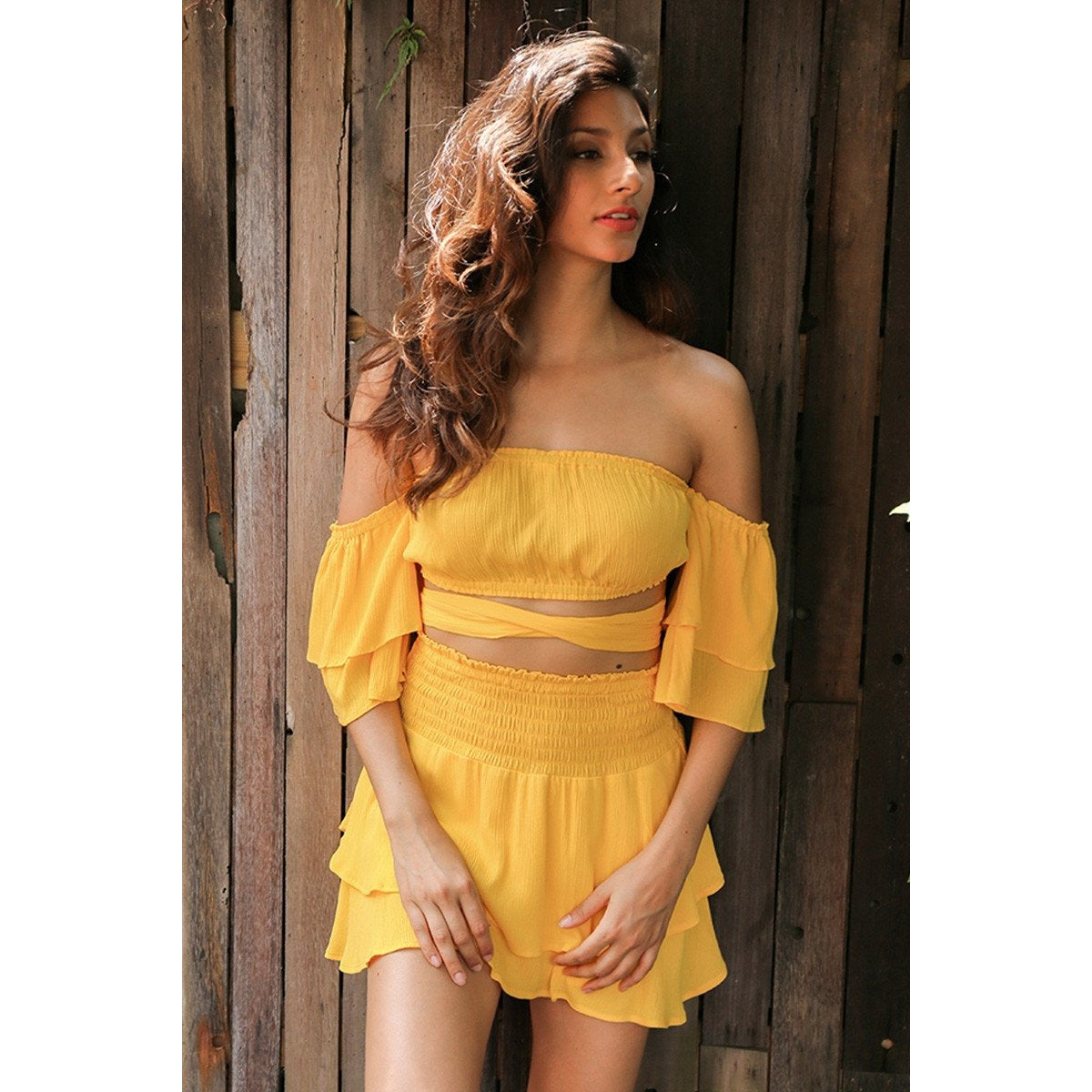 The Amani Romper is a unique design featuring a crop style bell sleeved top, sash waist tie, and an asymmetrical tiered ruffle bottom. Three colors available: yellow, red, and black.