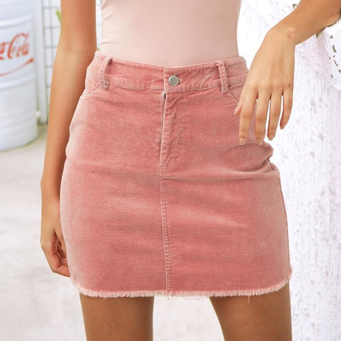 The Clara Corduroy Mini is a high waist, solid pink or black color straight pencil mini skirt, with belt loops, zipper and button front closure.