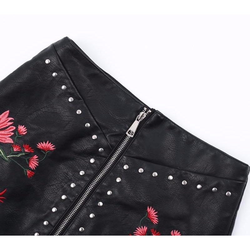 The Luciana Embroidered Mini is a black faux PU leather mini skirt with red floral embroidered print accompanied with a studded design border and central zipper closure.