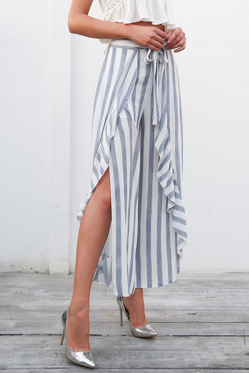 The Ilona Striped Side Split Pants feature a long split up the leg, an asymmetrical ruffled frill detail and vertical blueish-gray stripes. | Bohemian Fashion Clothing - Pants | Bijou Blossoms
