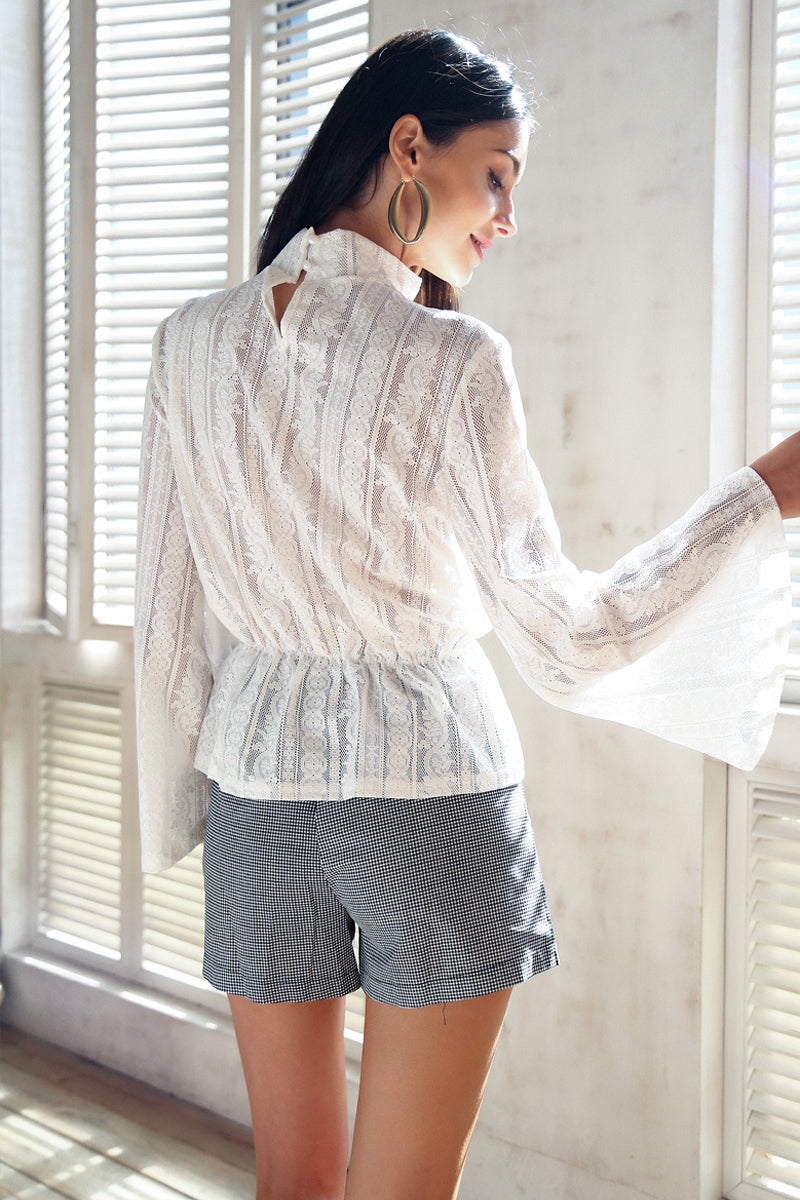 The Prudence Lace Blouse is a regular size top with long, flared sleeves and a transparent, vertical stripe design in solid colors. Available in white and navy blue, and four sizes: S, M, L, & XL.