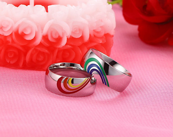 Set of 2 rainbow ring set, displaying a half heart in the colors of red, orange, and yellow. The other ring holds the other half of the heart displaying green, blue, and purple.
