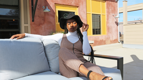 woman on white couch with a tan jumpsuit layered over a white long sleeve shirt and a black floppy hat