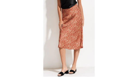 Woman in mid length red skirt with gold polka dots on a plane white background