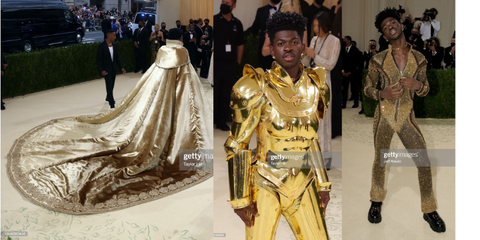 Lil nas x in three different looks. The first is a long train golden cape that looks like it came from royalty. The comes off to reveal a golden armor full body suit. Lastly the suit cracks open to reveal a black slim bodysuit that has golden bedazzle detailing covering every part.