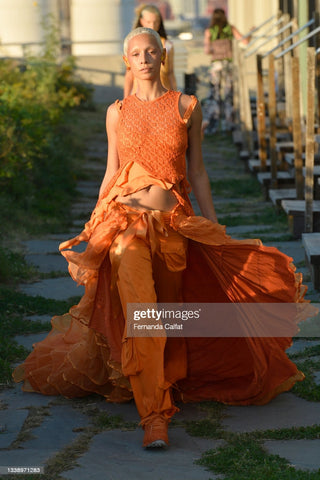 Model walking the runway with a blonde buzz cut wearing an orange jumpsuit with lots of ruffle detailing and a long train that flows behind them over their pants