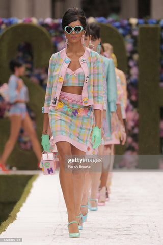 """Runway model in a two piece set that is colorful pastel plaid pattern with a skirt and a blazer that match. She is wearing sunglasses and a belt made of colorful block letters that spell """"Moschino"""""""