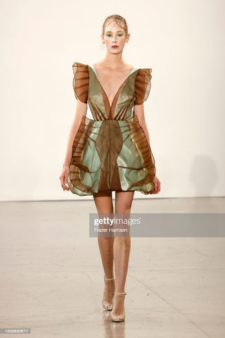 Runway look, model wearing a green shiny short aline dress with sheer brown detailing that extends past the shoulders and stretches. It looks like it is inspired by a butterfly.