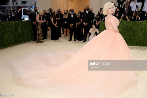 Billie Eilish in a large dramatic nude pink old fashion ball gown. She is wearing classic makeup and a long shag haircut