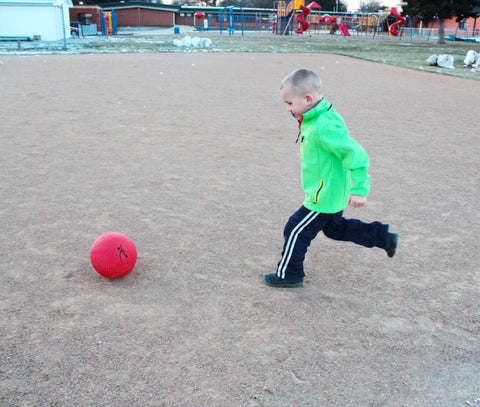 Boy kicking a playground ball