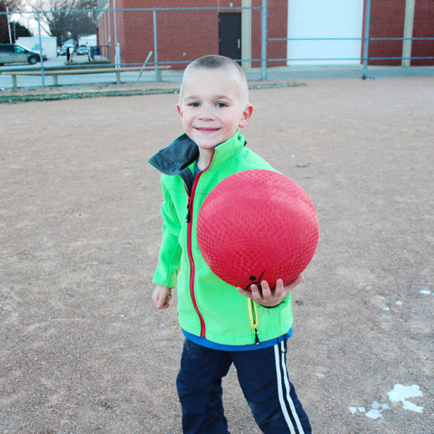 Boy holding out a playground ball