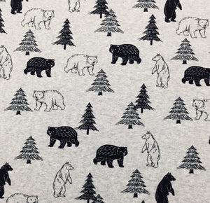 A variety of  silhouette and out lined bears and trees just over 1 in scattered throughout this cotton t-shit farbic with a light gray background. They look like very kind bears and happy trees